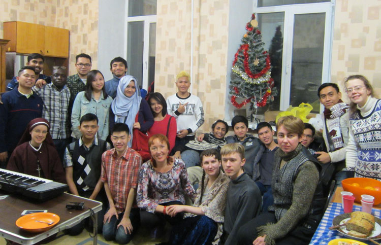 young adults gathered by Christmas tree