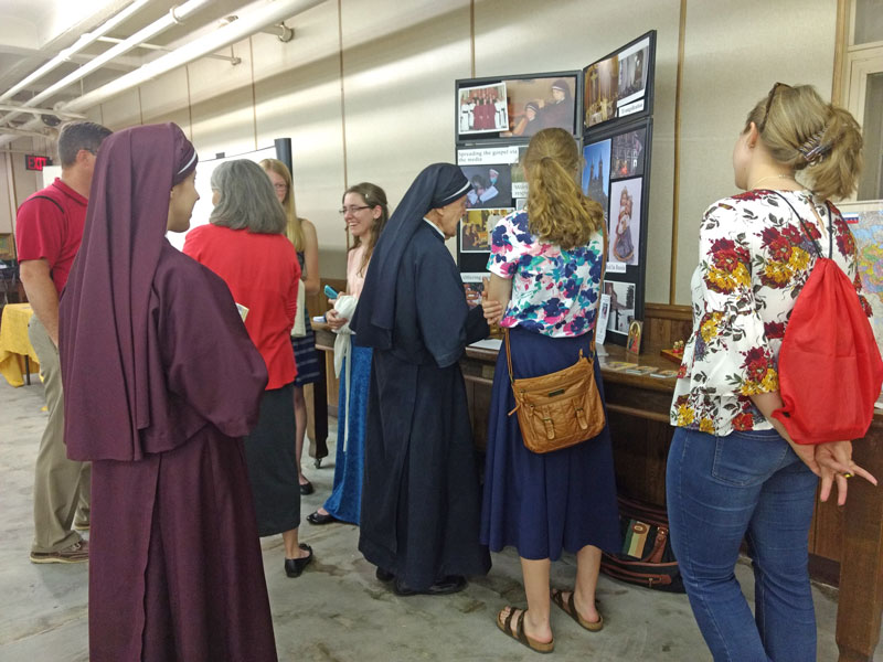 Sisters talking to attendees by display